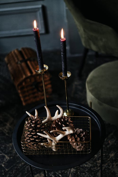 Pinecones and small horns on plate by candles