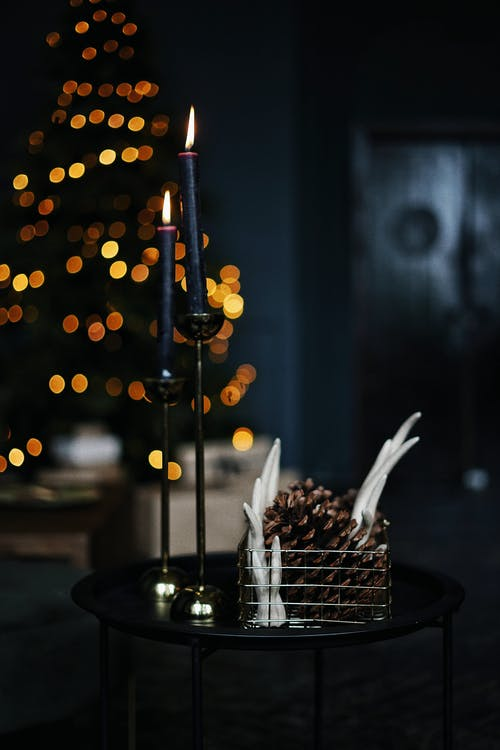 Candles and pinecones in room decorated with Christmas tree