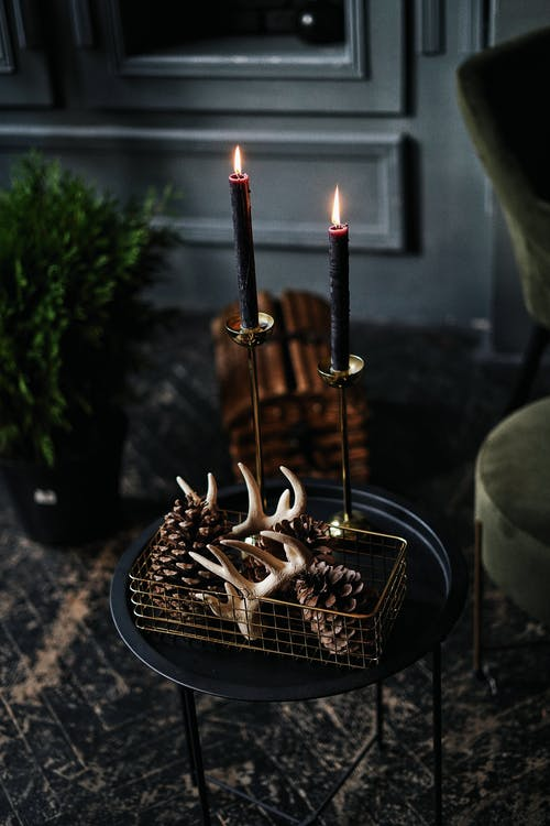 Horns and pinecones in box by flaming candles