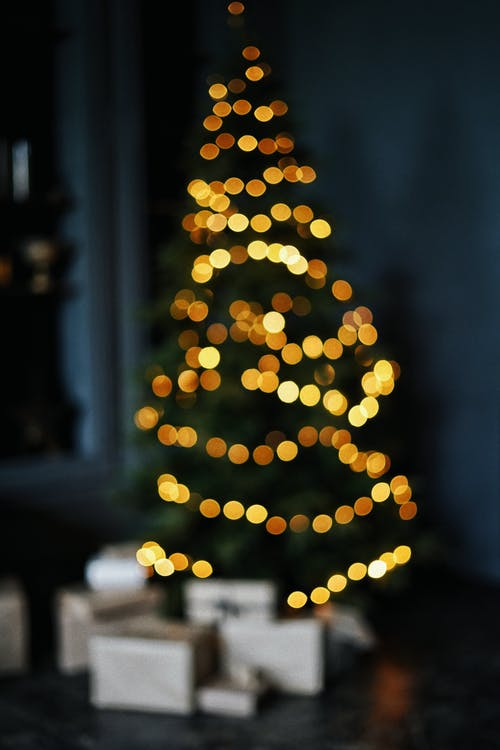Defocused bunch of boxes under tall green Christmas tree decorated with bright yellow glowing garlands