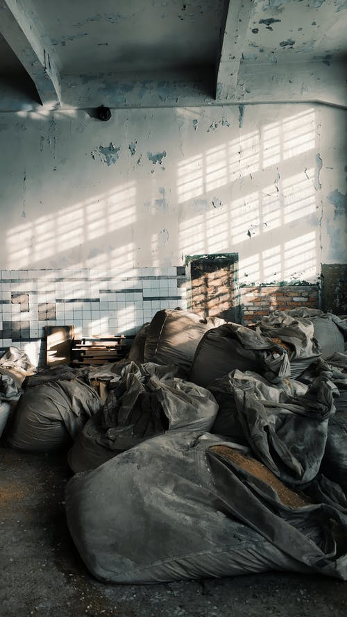 Aged abandoned house with cement walls and ceiling above pile of dirty bags in sunlight