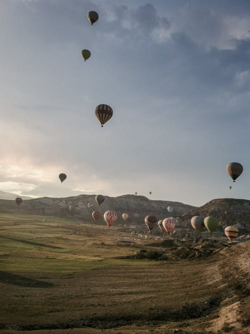Air balloons fly in sky over hills in Turkey