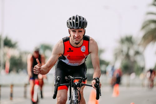 Muscular bicyclist with thumb up riding bike during competition