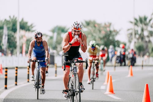 Fit male bicyclist drinking beverage while riding bicycle behind unrecognizable rivals during race on roadway in city
