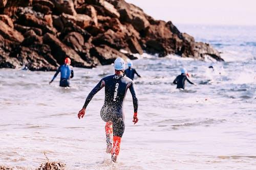Unrecognizable sportsmen in wet suits swimming in foamy ocean