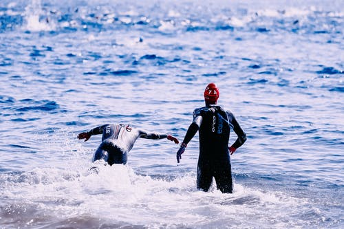 Faceless athletes swimming in shiny foamy sea in daylight