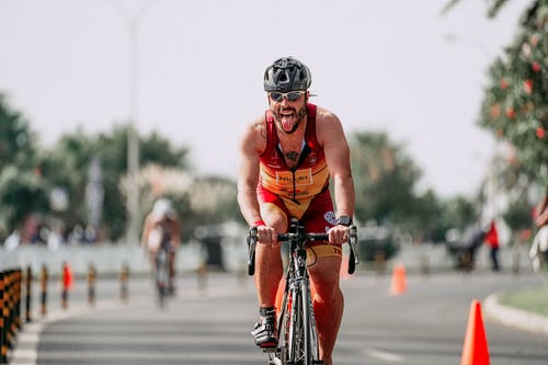 Fit sportsman in protective helmet and cycling glasses riding bicycle on road during competition
