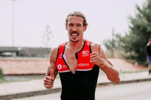 Strong sportsman running on asphalt road