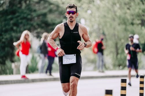 Strong muscular sportsman in sportswear and protective glasses running on asphalt road during competition