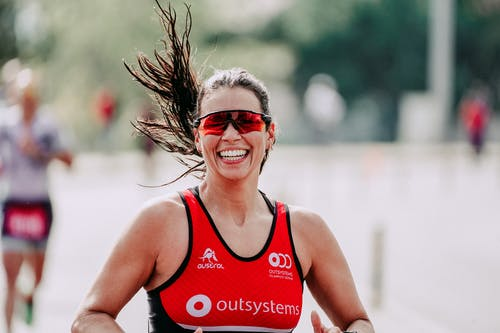 Happy female athlete in sportswear and protective glasses smiling while running on road during competition