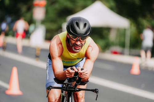 Smiling man in sportswear and helmet competing on bicycle riding on asphalt road