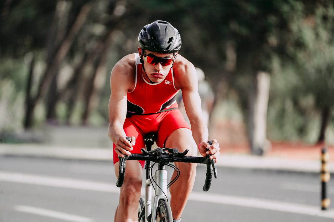 Young muscular man in helmet and sportswear cycling on asphalt road during competition