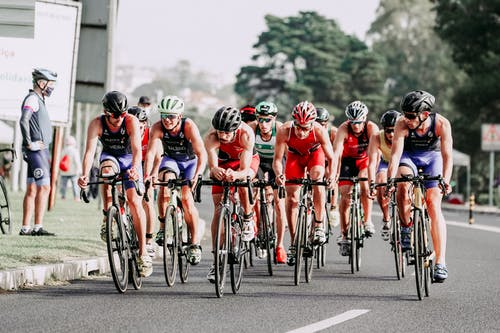 Group of cyclists in helmets riding professional bicycles fast on track during race