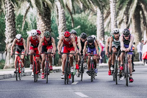 Group of people in protective helmets and sportswear riding bikes on asphalt road during competition