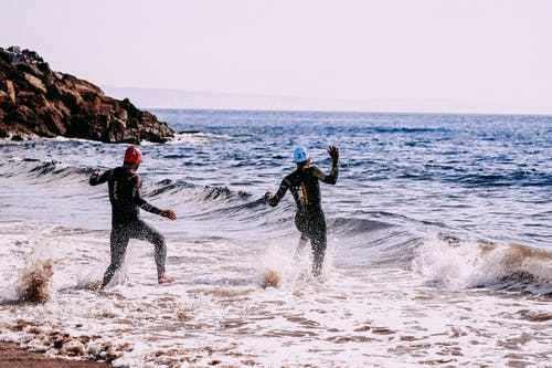 Anonymous sportspeople running into sea