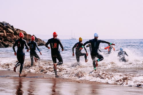 Faceless sportspeople in wetsuits entering sea