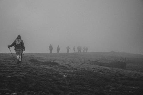Group of people with backpacks hiking in mountainous terrain covered with thick dense fog