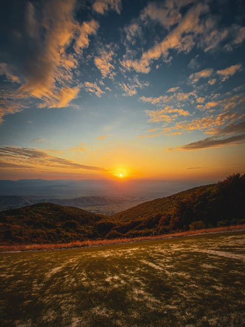Picturesque scenery of green field in mountainous terrain with trees under cloudy blue sky at sunset