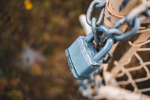 Chain link fence closed with lock in countryside