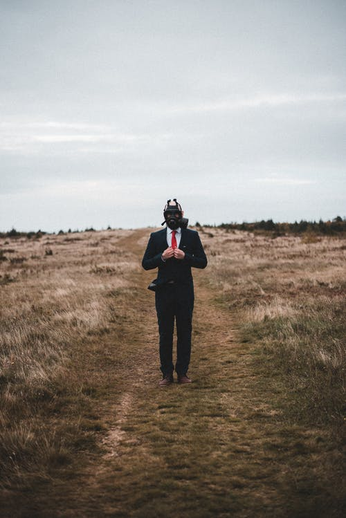 Full body of man wearing elegant suit and gas mask standing in meadow with dry grass under cloudy sky