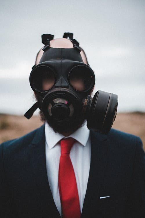Businessman in gas mask on street