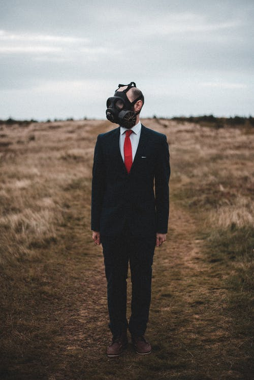 Full body of anonymous businessman in formal suit and gas mask standing in field with dry grass in countryside in cloudy day
