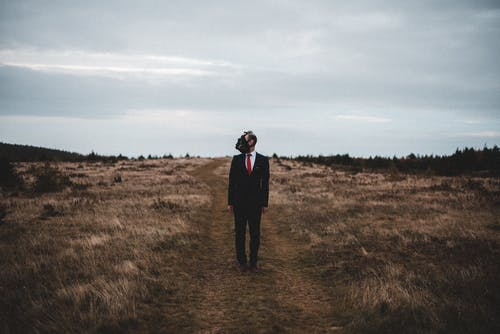 Stylish man in suit and gas mask standing in countryside