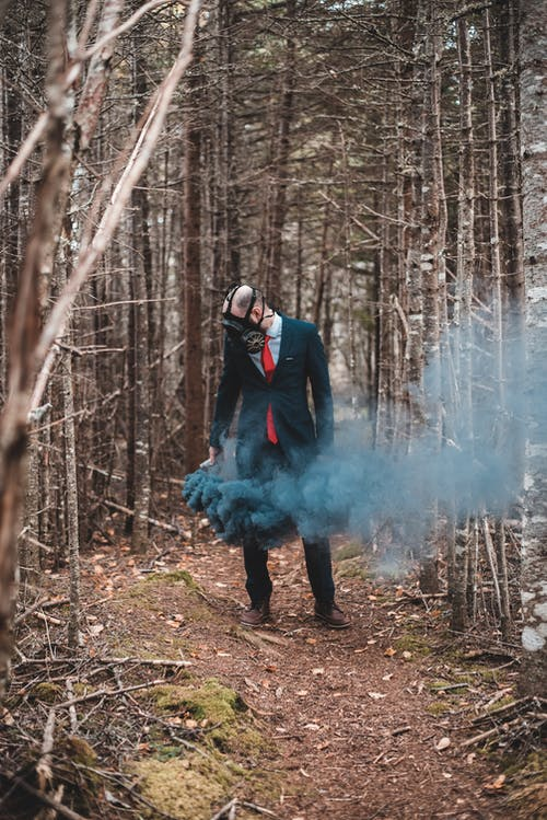 Anonymous businessman in stylish suit and gas mask standing with black smoke bomb in hand among trees