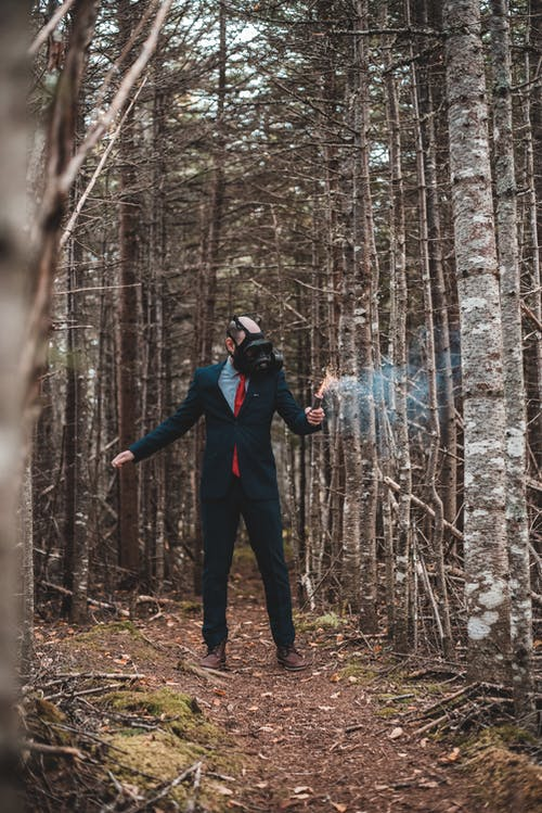 Man in stylish suit and gas mask standing in forest