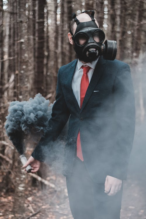 Confident anonymous man wearing classy suit and gas mask standing with black smoke bomb in hand against trees