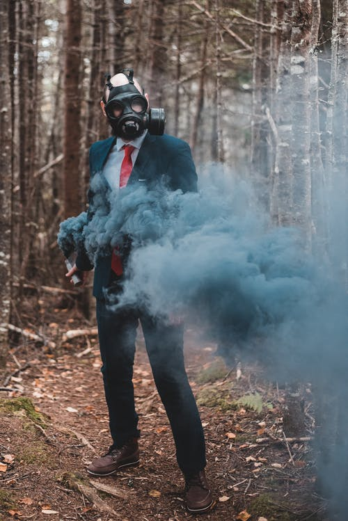 Confident man in gas mask with black smoke bomb