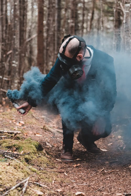 Confident man in protective gas mask squatting down with black color bomb in hand against trees in forest