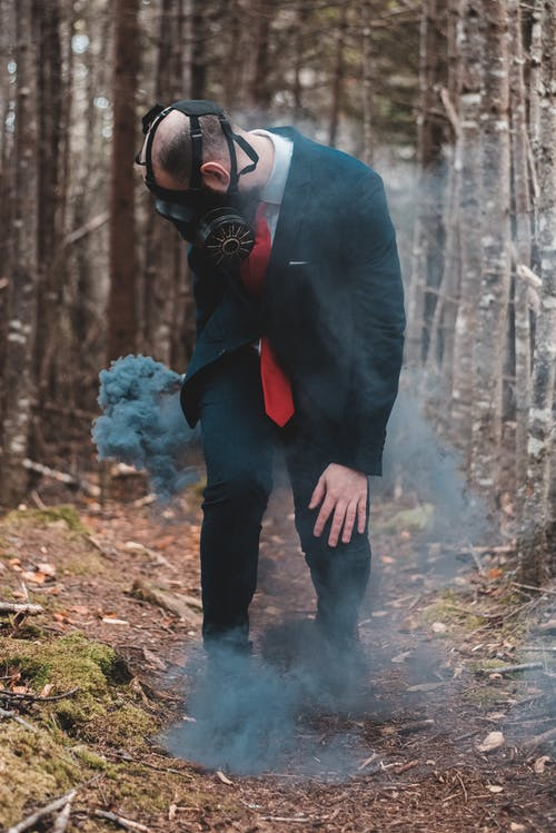 Formal man standing with smoke bomb in forest