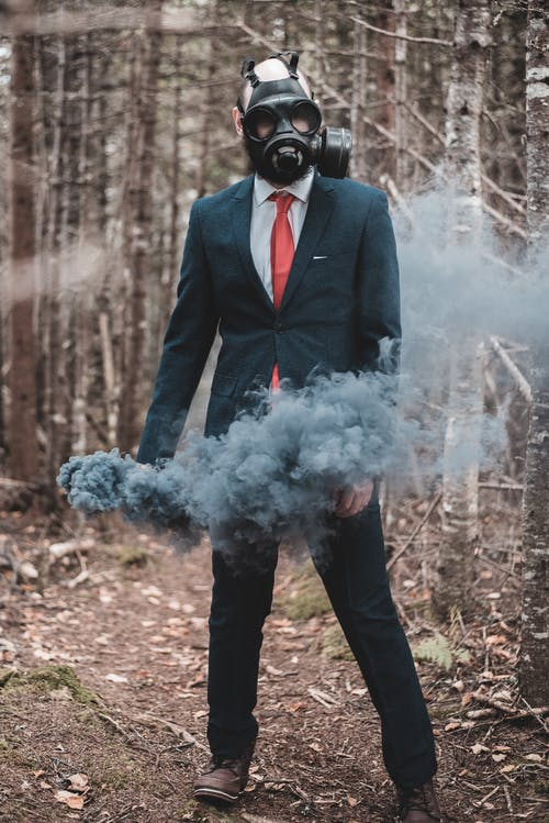 Full body man in formal suit and protective mask standing in spooky forest with gray colored smoke