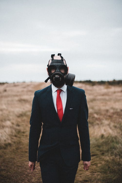 Formal man in gas mask in overcast countryside