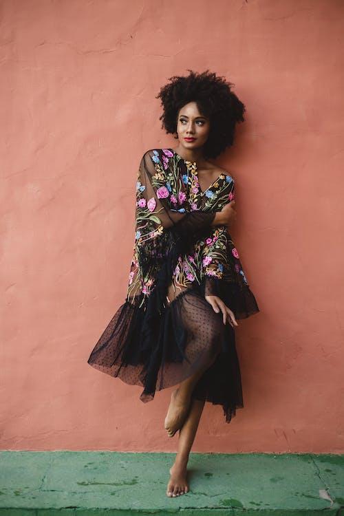 Stylish dreamy black woman with makeup near street wall