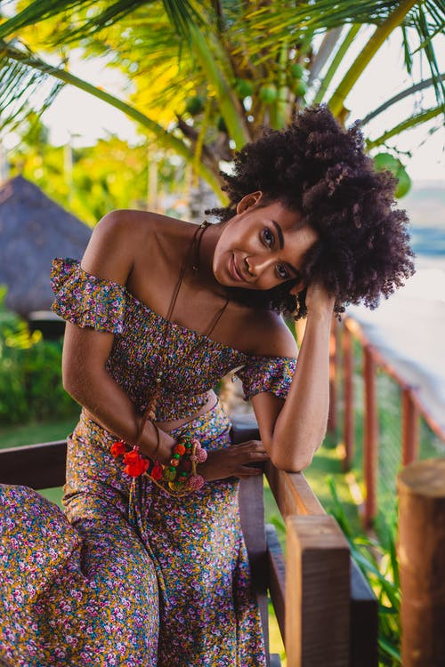 Young smiling African American female in stylish dress and beads with Afro hairstyle leaning on hand while looking at camera