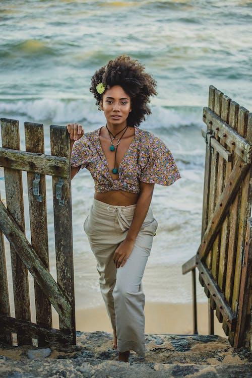 Trendy black woman on stairs behind sea in summer