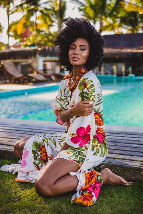 Young sensitive black female in trendy outfit with Afro hairstyle sitting on wooden boardwalk near swimming pool and looking at camera