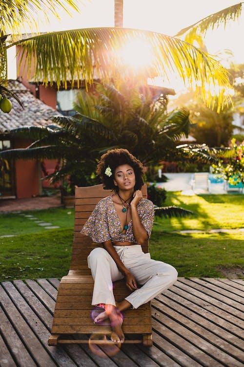 Trendy black female traveler resting on sun bed in evening