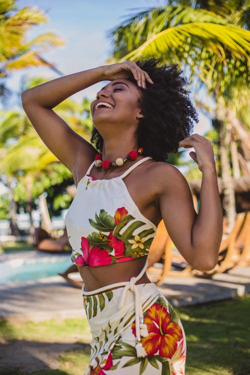 Young cheerful African American lady in trendy outfit with Afro hairstyle touching hair with closed eyes