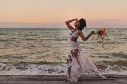 Side view of young glad black female in elegant dress with flower bouquet touching forehead near sea at sunset