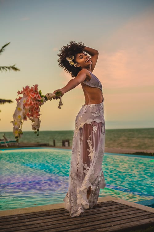 Side view of young content black woman in bridal dress with flower bouquet touching hair on boardwalk near swimming pool in twilight