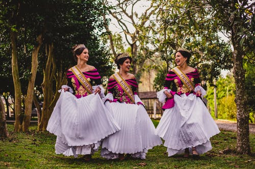 Happy ethnic girlfriends in stylish dresses and crowns on lawn
