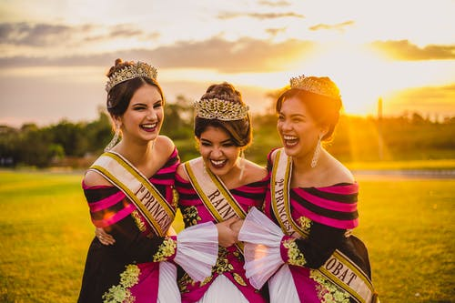 Laughing ethnic women in bright trendy apparel and crowns embracing on meadow under glowing cloudy sky at sunset in back lit