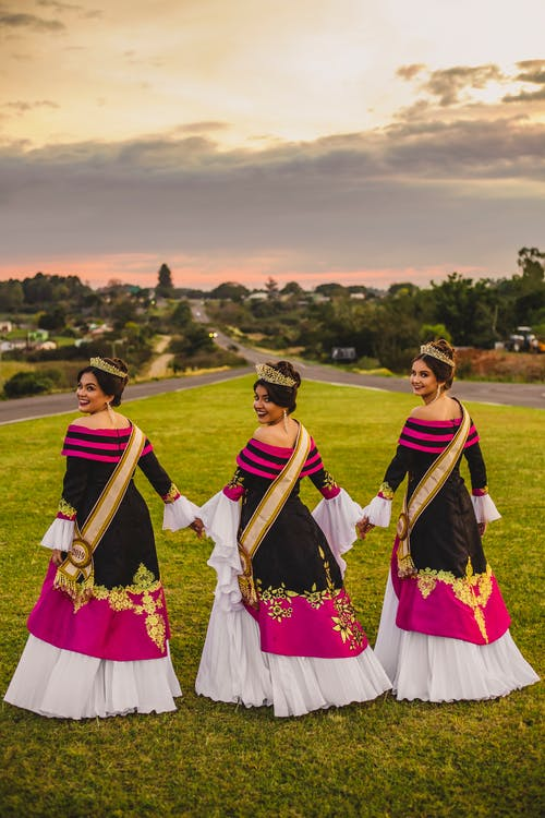 Stylish ethnic girlfriends on lawn after winning in beauty contest
