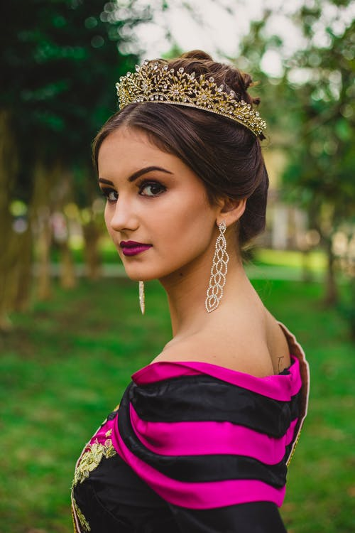 Side view of young attentive woman in crown and earrings looking at camera on lawn in park