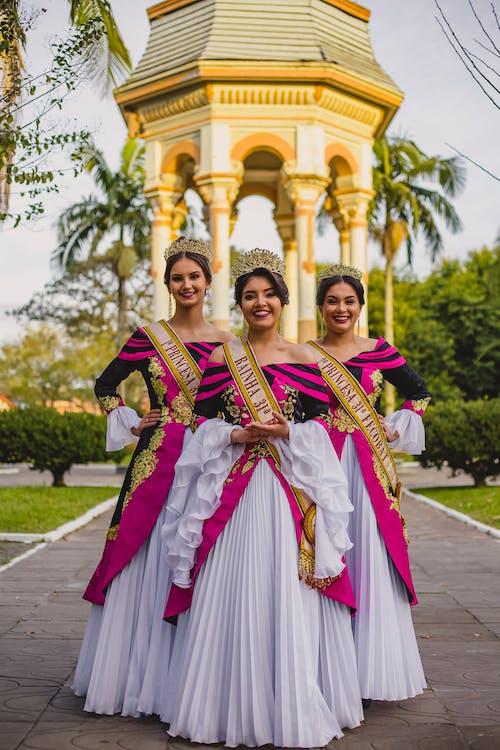 Stylish ethnic beauty contest winners on walkway in city