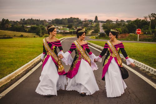 Young positive ethnic women in stylish apparel and crowns looking at each other on roadway after winning in beauty contest