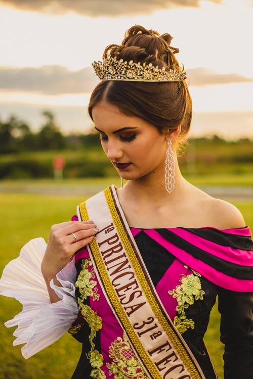 Stylish beauty contest winner in crown and ribbon in countryside